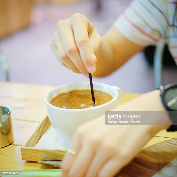 Cropped Image Of Person Stirring Coffee At Table
