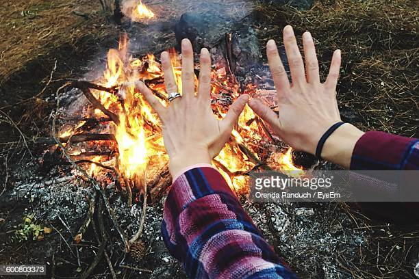 Cropped Image Of Person Warming Hands By Campfire