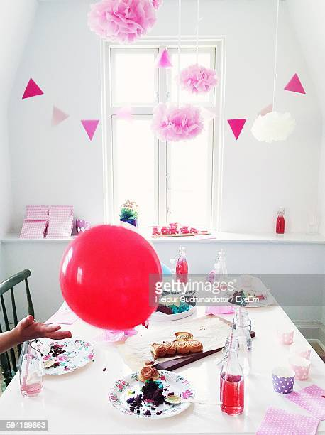 Cropped Image Of Person With Balloon At Birthday Party