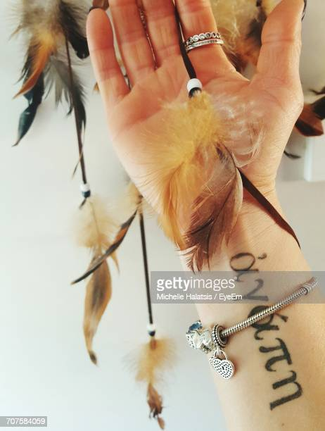 Cropped Image Of Person With Tattoo On Hand Holding Feather