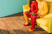 cropped image of retro styled girls in colorful dresses sitting with plates of broccoli at home