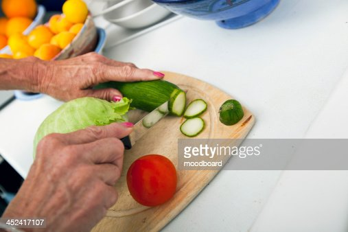 Cropped image of senior woman cutting vegetables on chopping board in kitchen : Foto stock