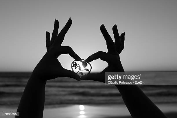 Cropped Image Of Silhouette Hands Holding Heart Shaped Locket Against Sky