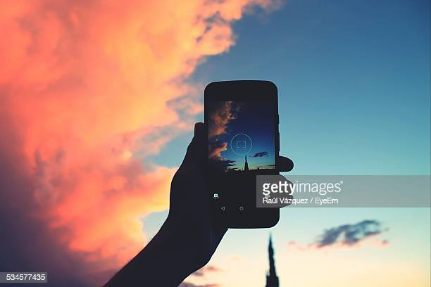 Cropped Image Of Silhouette Person Holding Cell Phone Against Sky At Dusk