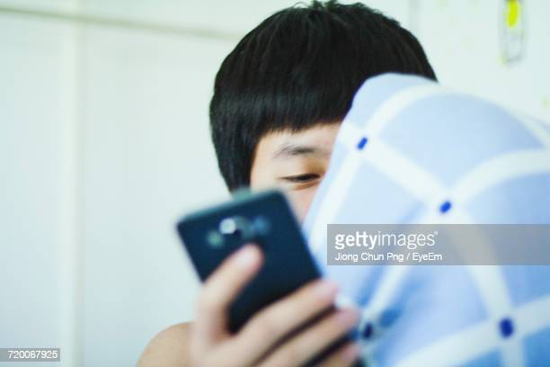 Cropped Image Of Teenage Boy Holding Mobile Phone At Home