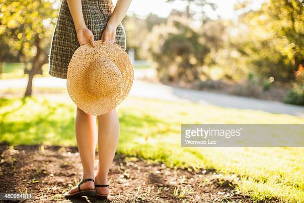 Cropped image of teenage girl holding sunhat behind her back