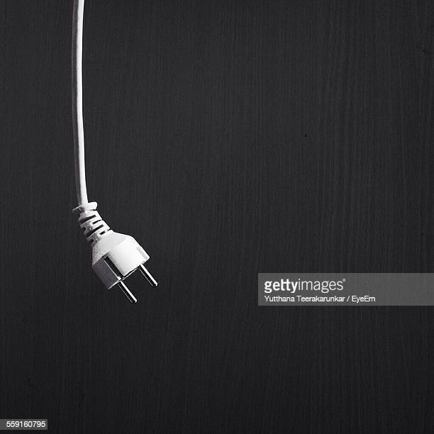 Cropped Image Of Three Pin Plug Hanging Against Wooden Wall