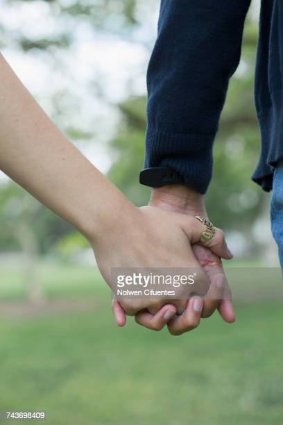 Cropped image of two young women holding hands