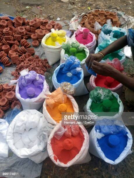 Cropped Image Of Vendor Hand Tying Powdered Color At Market