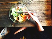 Cropped Image Of Woman Eating Fresh Salad At Wooden Table