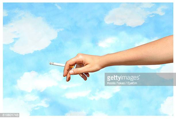 Cropped image of woman hand holding cigarette against cloudy sky