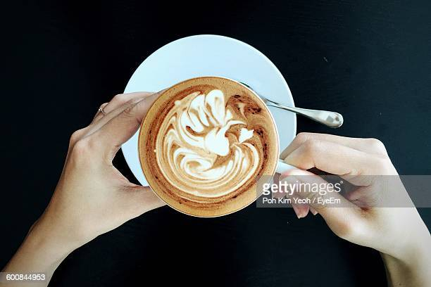 Cropped Image Of Woman Hand Holding Fresh Coffee Cup On Table At Cafe