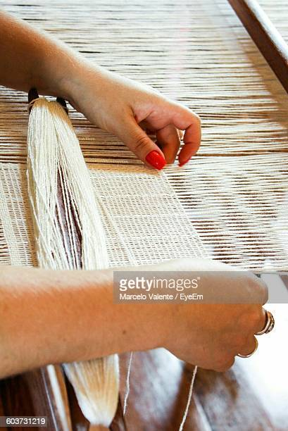 Cropped Image Of Woman Hands Weaving Threads At Factory