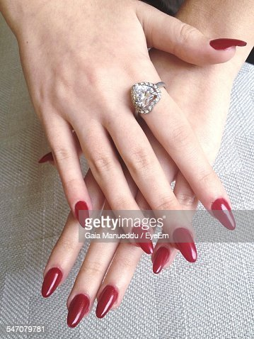 Cropped Image Of Woman Hands With Red Nail Polish Wearing Heart Shape Ring