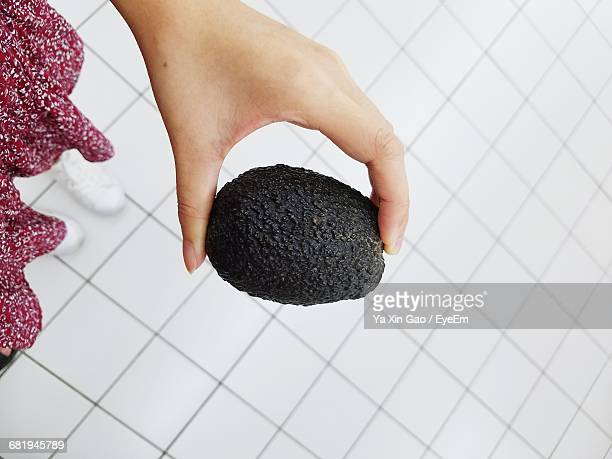 Cropped Image Of Woman Holding Black Avocado