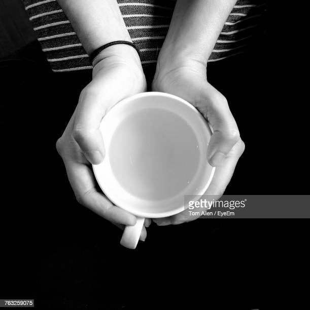 Cropped Image Of Woman Holding Cup Over Black Background
