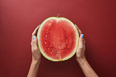 cropped image of woman holding half of watermelon above red surface