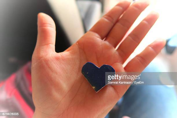 Cropped Image Of Woman Holding Heart Shape Decoration