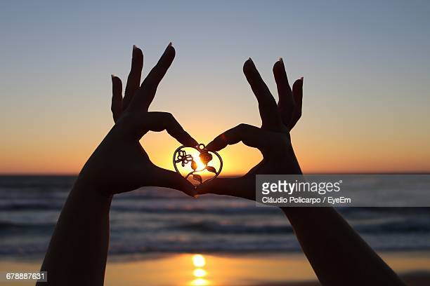 Cropped Image Of Woman Holding Heart Shape Locket Against Clear Sky During Sunset