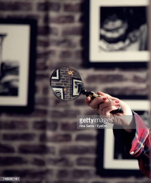 Cropped Image Of Woman Holding Magnifying Glass Against Wall