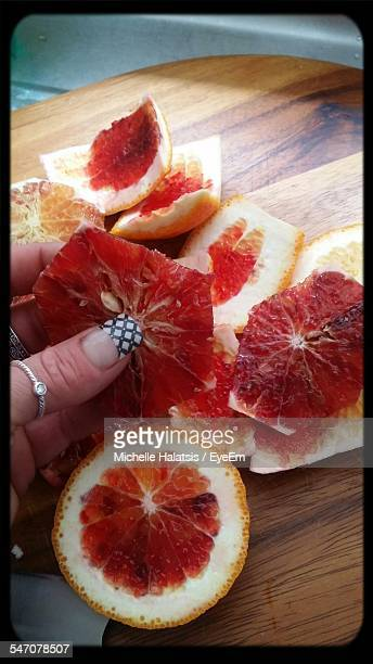 Cropped Image Of Woman Holding Slice Of Blood Orange At Home