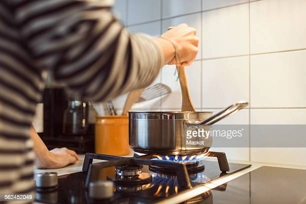 Cropped image of woman holding spatula in sauce pan while cooking food on stove