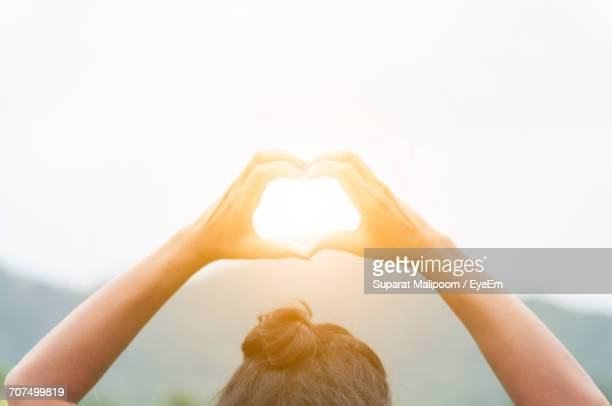 Cropped Image Of Woman Making Heart Shape Against Bright Sun