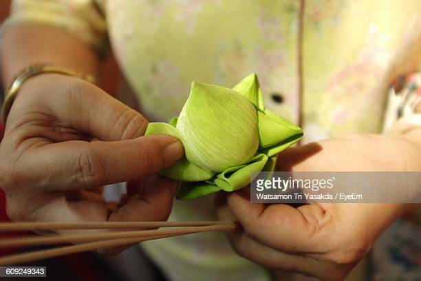 Cropped Image Of Woman Making Lotus Flower From Leaf At Temple