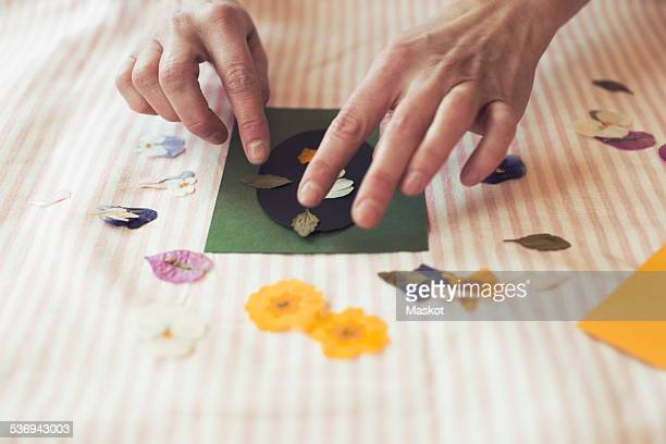 Cropped image of woman making paper craft product on table