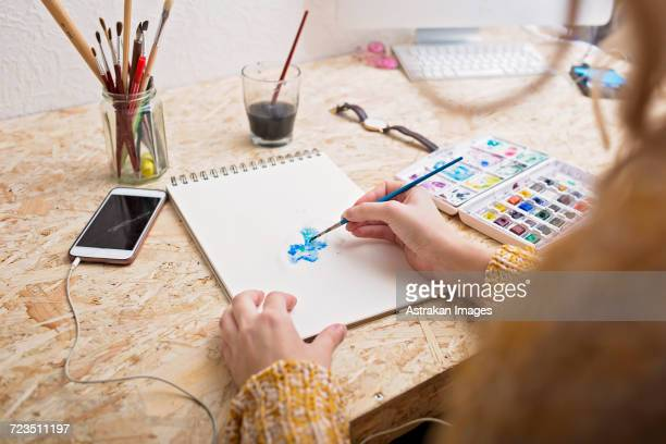 Cropped image of woman painting on notepad at table
