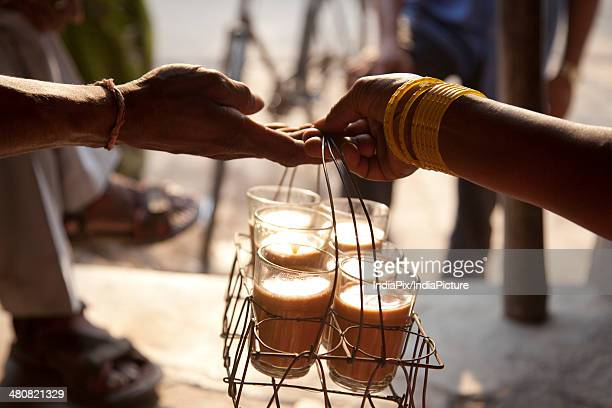 Cropped image of woman passing tray of chai to man at stall