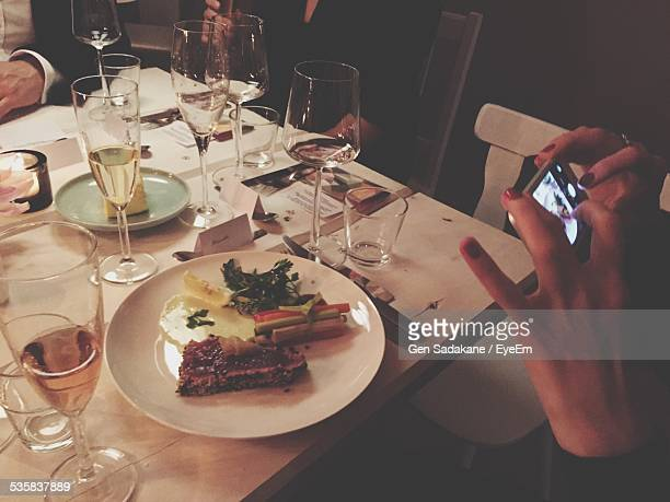 Cropped Image Of Woman Photographing Food On Table At Restaurant