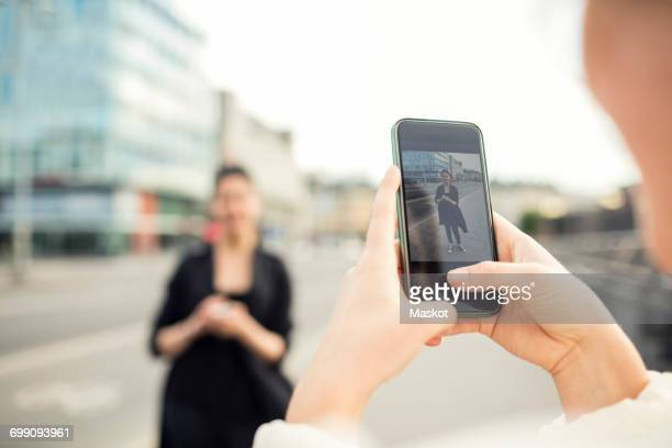 Cropped image of woman photographing friend in city