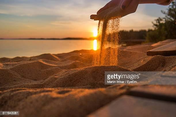 Cropped image of woman pouring sand in beach