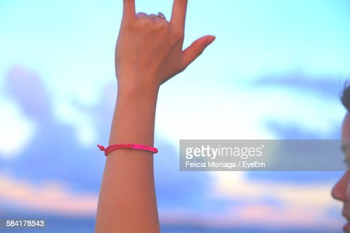Cropped Image Of Woman Showing Rock Music Sign At Sunset