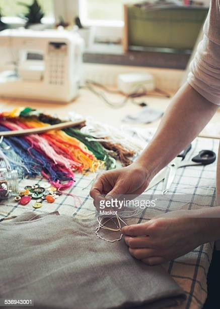 Cropped image of woman stitching fabric on table at home