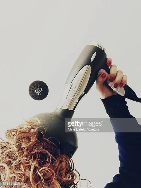 Cropped image of woman using hair dryer with pump