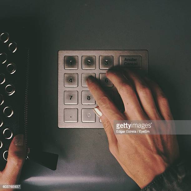 Cropped Image Of Woman Using Keypad On Atm
