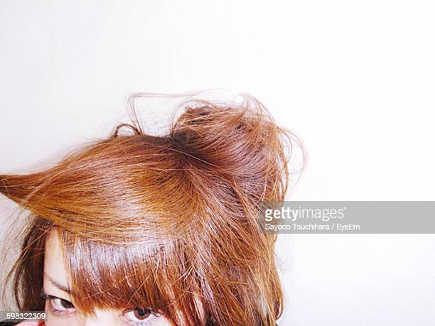 Cropped Image Of Woman With Brown Hair Against White Wall