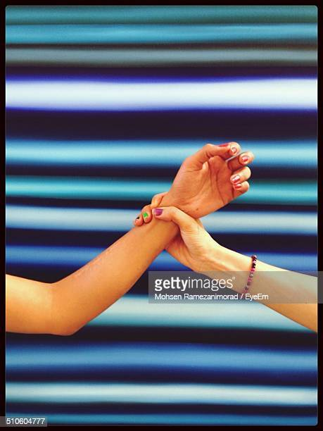 Cropped image of women holding hands against colored background