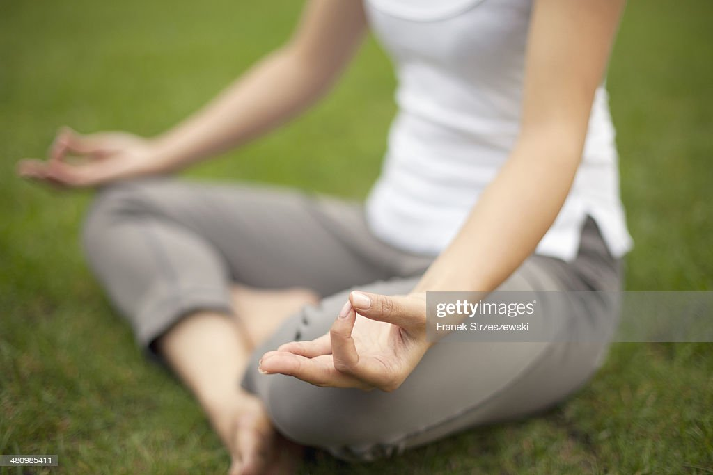 Cropped image of young woman in park practicing lotus position