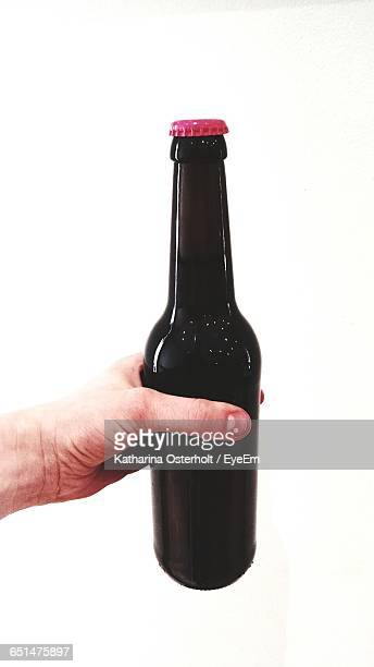 Cropped Imaged Person Holding Beer Bottle Against White Background