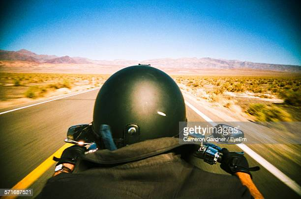 Cropped Man Riding Motorbike On Country Road