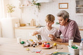 Waist up of grandbmother and her grandson coloring Easter eggs. Family traditions concept