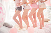 Cropped portrait of charming, fit, slender, smooth legs of girls holding hands on waist standing in a line, bending knees wearing night wear celebrating birthday, event, holiday indoor