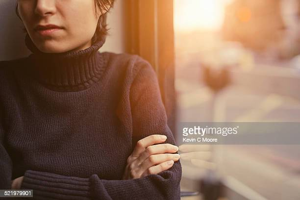 Cropped portrait of young woman with arms folded next to window