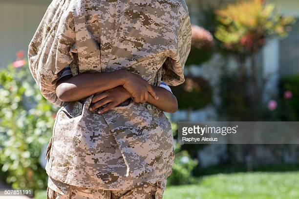 Cropped rear view of female soldier hugging son on homecoming