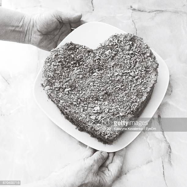 Cropped Senior Woman Hand With Heart Shape Cake In Plate At House