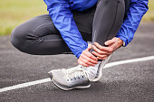 Cropped shot of a young man holding his ankle in pain while running.