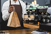 cropped shot of african american barista holding disposable coffee cups and paper bags in cafe